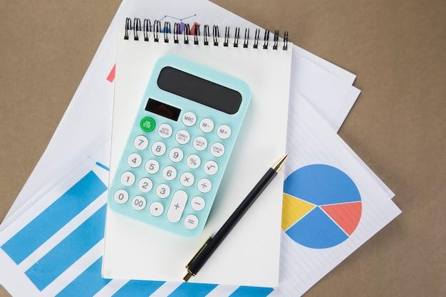 Sul desktop con blocco note, calcolatrice, carta e bicchieri. concetto di desktop Foto Premium