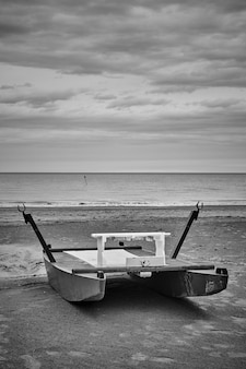 Spiaggia desolata con barca di salvataggio in riva al mare. rimini, italia. fotografia in bianco e nero, paesaggio