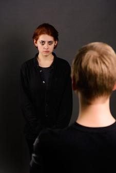 Giovane donna disperata con uomo aggressivo in studio, concezione di violenza domestica