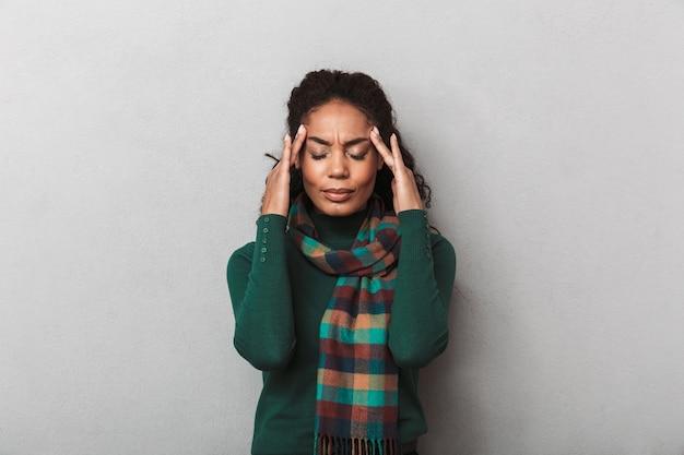 Donna africana disperata che indossa un maglione in piedi, che soffre di una forte emicrania