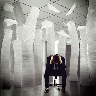 Uomo d'affari disperato seduto tra pile di carte