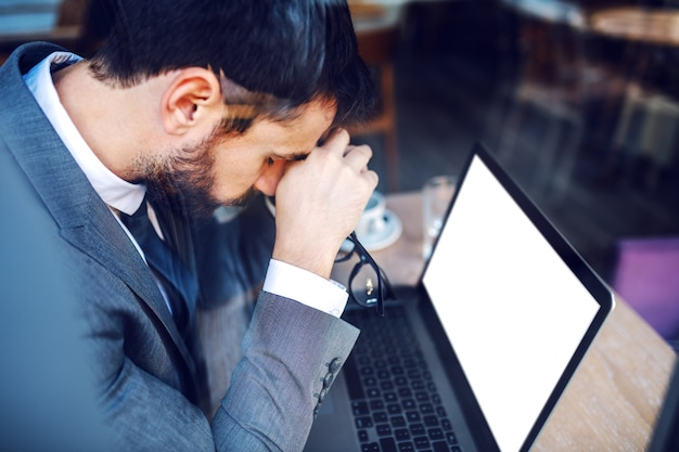 Giovane uomo d'affari elegante caucasico disperato in vestito che tiene la sua testa e pensa a come trovare una soluzione per il problema. sul tavolo c'è il laptop.