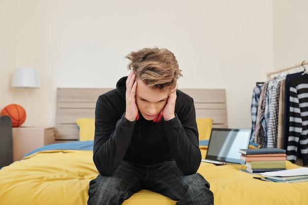 Studente di liceo disperato seduto sul bordo del letto stressato a causa di esami e test