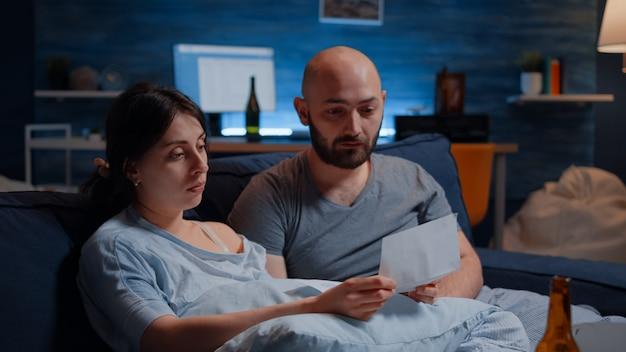 Disperato giovane coppia lettura avviso di sfratto in scartoffie letter