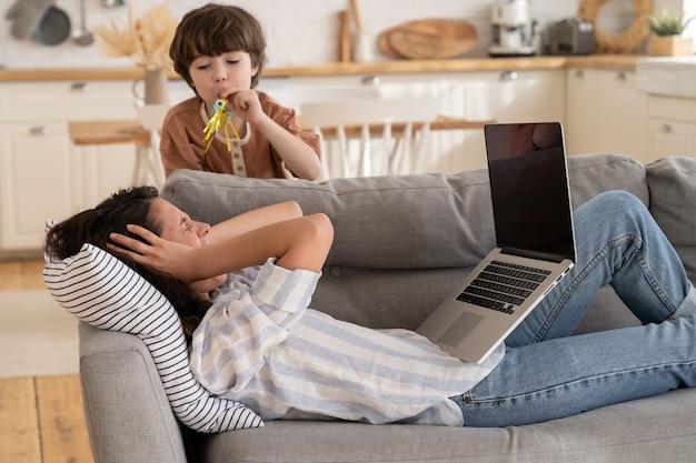 La giovane madre disperata copre le orecchie urlando infastidita dal cattivo comportamento del figlio piccolo che i genitori lavorano da casa