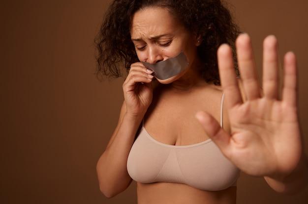 Donna che piange disperatamente spaventata con le lacrime agli occhi, con la bocca sigillata mostra il segnale di stop con la mano alla telecamera, si erge su sfondo beige scuro. concetto sociale di porre fine alla violenza contro le donne