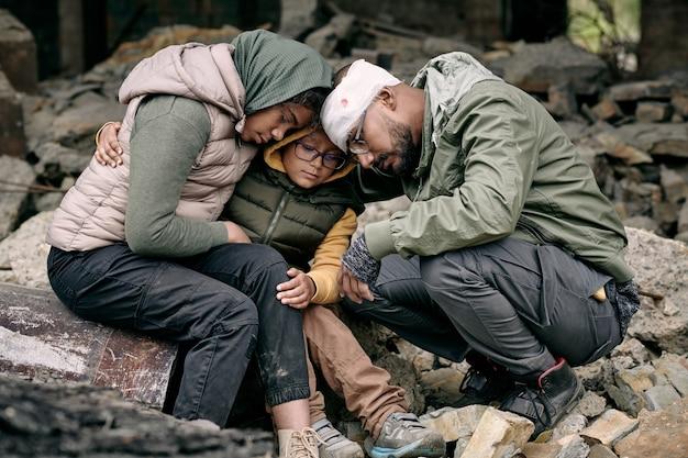 Famiglia araba scoraggiata che si siede sulle rovine della casa e che si abbraccia dopo la guerra delle ostilità con...