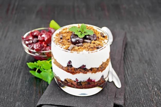Dessert foresta nera di ciliegie, biscotto al cioccolato e ricotta morbida con crema in un bicchiere su tovagliolo, menta, frutti di bosco in una ciotola e un cucchiaio su fondo di legno nero