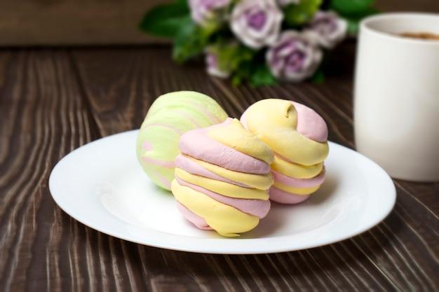 Dessert marshmallow o zephyr, sul tavolo e una tazza di caffè espresso caldo. il concetto di dolci sani