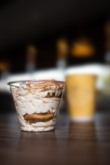 Dessert in un bicchiere di plastica contro la superficie del caffè in un bar.