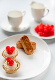 Dessert di ciliegie dolci con dita di mandorle e due cestini di torte