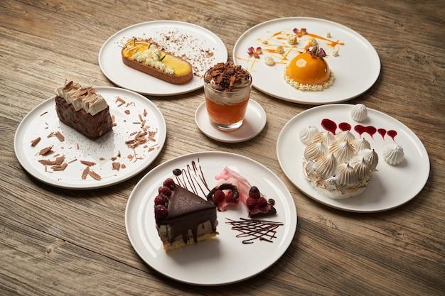 Tavolo da dessert con cupcake, mousse, biscotti, cheesecake. pezzo di torte su un piatto bianco sul fondo della tavola in legno