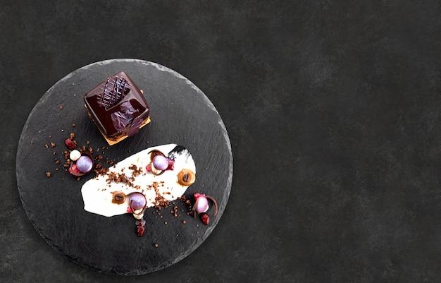 Dessert con noci in glassa di cioccolato a forma di cubo su ardesia nera