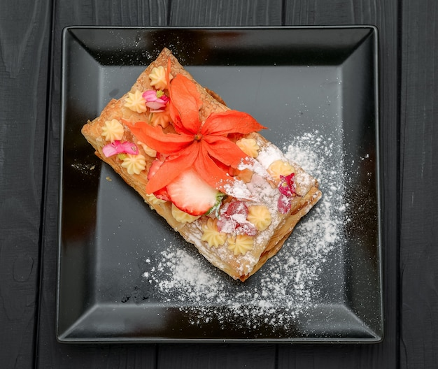 Dessert con pasta sfoglia, panna e fragole su una superficie nera