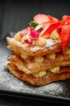 Dessert con pasta sfoglia, panna e fragole su fondo nero