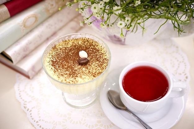 Dessert con tè sul tavolo con fiori e libri.