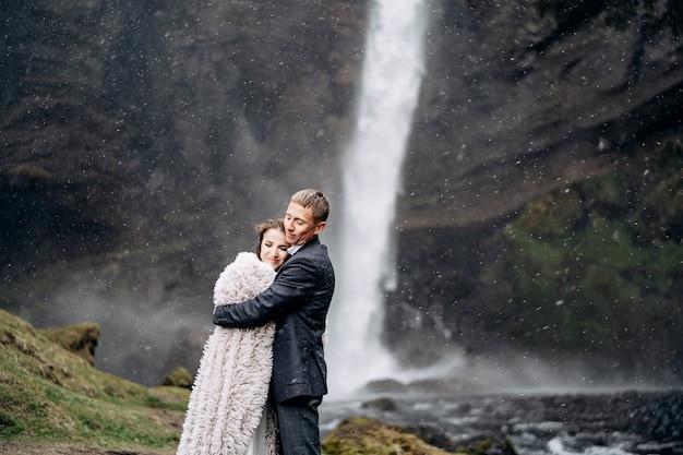 Matrimonio islandese di destinazione vicino alla cascata di kvernufoss la coppia di sposi è in piedi vicino alla cascata