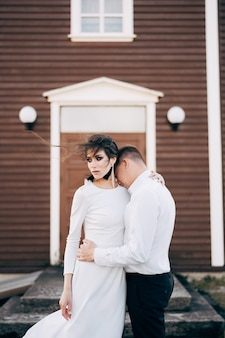 Destinazione islanda matrimonio sposi davanti a una chiesa nera lo sposo abbraccia la sposa