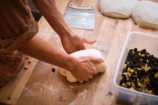 Dettaglio delle mani di un fornaio che introducono gli ingredienti nell'impasto del pane