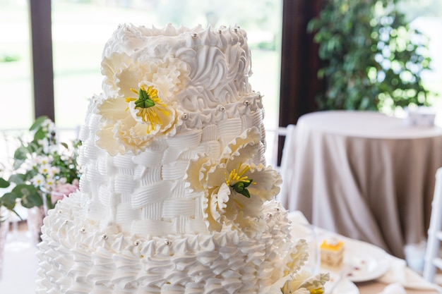 Dettaglio di una bella torta di crema nuziale decorata con fiori di fondente su un tavolo di celebrazione del matrimonio