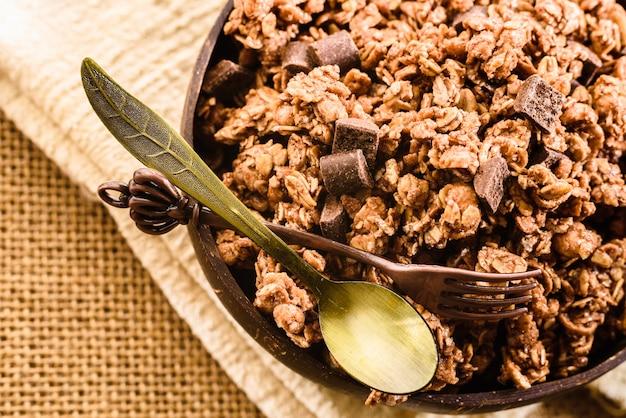 Dettaglio di una ciotola con calde tonalità di farina d'avena e muesli al cioccolato.