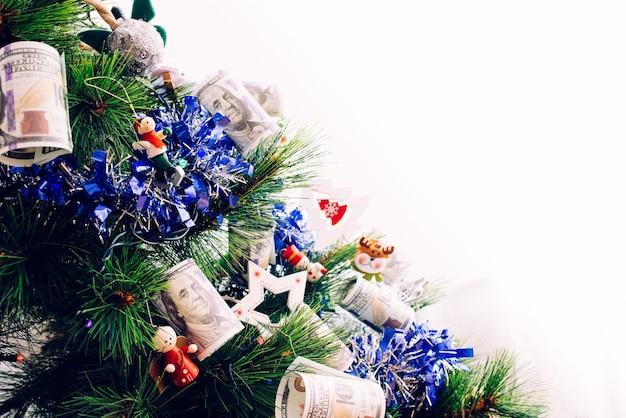 Dettaglio dell'albero di natale con decorazioni e banconote da un dollaro che desiderano guadagnare soldi alla vigilia di capodanno, con spazio vuoto per copia.