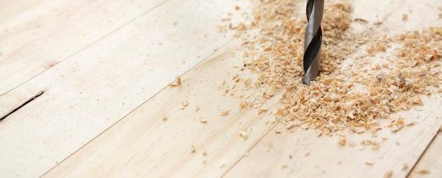 Particolare punta trapano foratura doghe legno naturale.