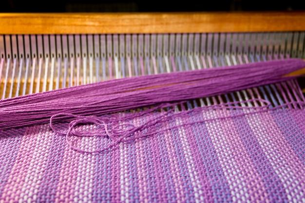 Dettaglio del tessuto in telaio a pettine con colori ultravioletti e lilla