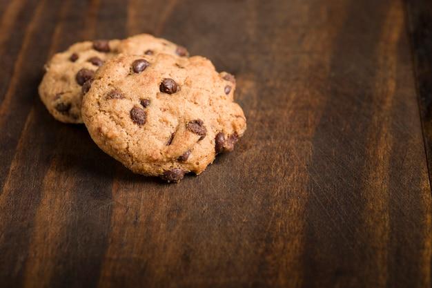 Dettaglio di biscotti artigianali senza glutine con pepite di cioccolato su fondo rustico in legno