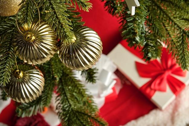 Dettaglio delle palle dorate dell'albero di natale con il regalo nel fondo non focalizzato