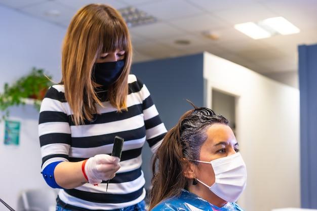 Dettaglio del parrucchiere con maschera che applica la tintura al cliente con maschera. riapertura con misure di sicurezza dei parrucchieri nella pandemia covid-19, coronavirus