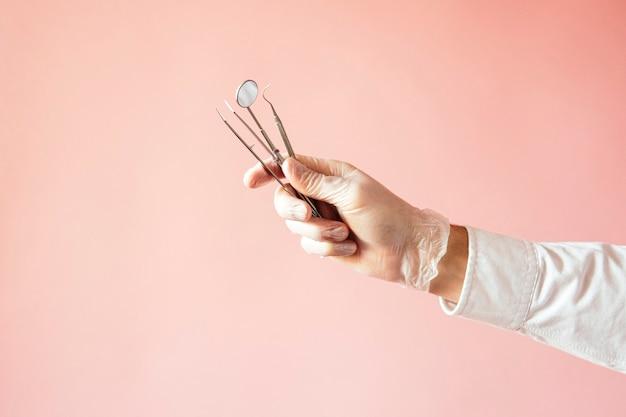 Dettaglio della mano che tiene gli strumenti dentali in clinica odontoiatrica, con sfondo rosa. clinica dentale.