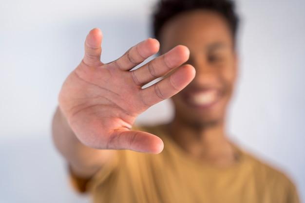 Dettaglio della mano spalancata nella parte anteriore che raggiunge una persona. uomo afroamericano irriconoscibile che fa un segno di tocco con la mano. ferma il razzismo e abbraccia diverse etnie. Foto Premium