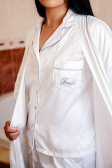 Dettaglio delle mani di una sposa irriconoscibile che mostra il suo pigiama e la veste da sposa
