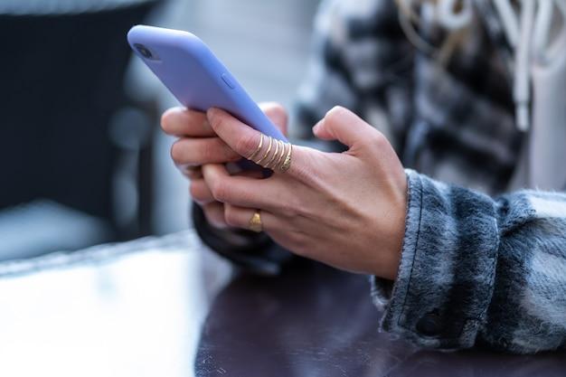 Particolare delle mani di una donna con uno smartphone con cover in gomma