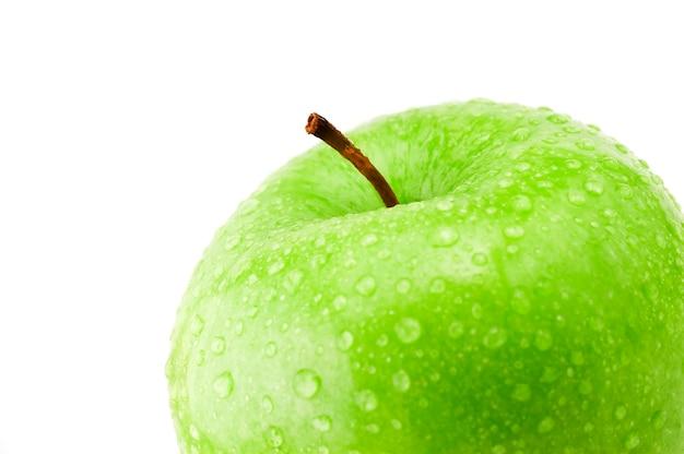 Dettaglio di una sana mela verde con acqua fresca scende isolato su bianco