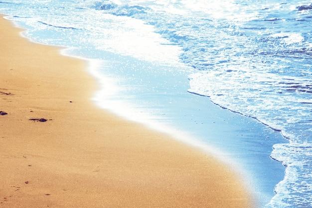 Dettaglio dei piedi umani nella sabbia dorata in spiaggia. viaggio estivo e concetto di vacanza.