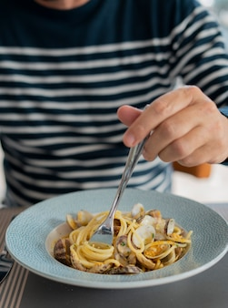 Dettaglio maschio mano mangiare pasta spaghetti con vongole e triglie, cucina mediterranea