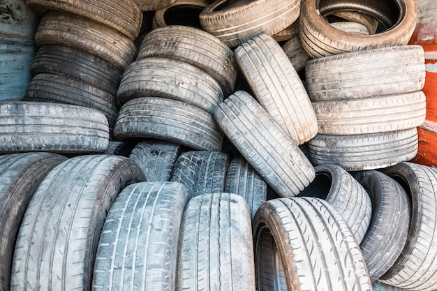Dettaglio di vecchi pneumatici usati e ritirati, accatastati in un impianto di trattamento.