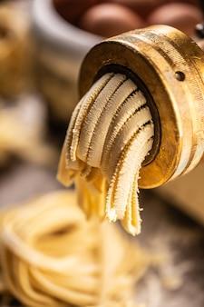 Dettaglio di una presa di pasta con i bordi a zigzag di fettuccine in uscita.