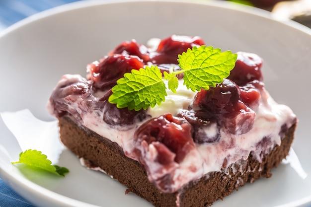 Dettaglio di un pezzo di brownie con crema, ciliegie e foglie di menta fresca su un piatto.