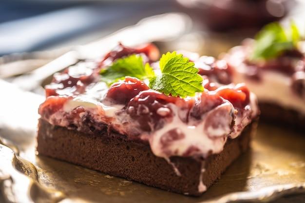 Dettaglio di un pezzo di brownie con crema, ciliegie e foglie di menta fresca.