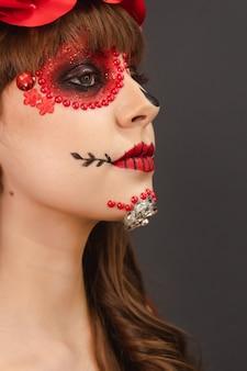 Dettaglio ritratto di una bella ragazza con il trucco dia de los muertos con sfondo grigio.