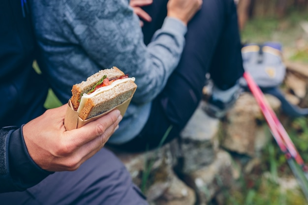 Particolare di un panino che una coppia sta per mangiare facendo una sosta per fare trekking