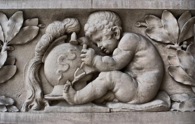 Particolare di una facciata scolpita del grand palais che mostra un bambino che scolpisce nella pietra