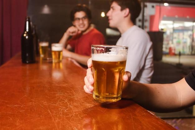 Dettaglio di un uomo che tiene in mano un bicchiere di birra con i suoi amici al bar.