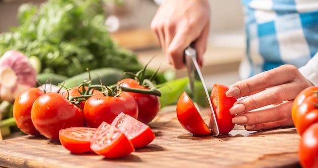 Particolare di un pomodoro appena tagliato a metà su un tagliere con a parte cetriolo, aglio e altri pomodori.