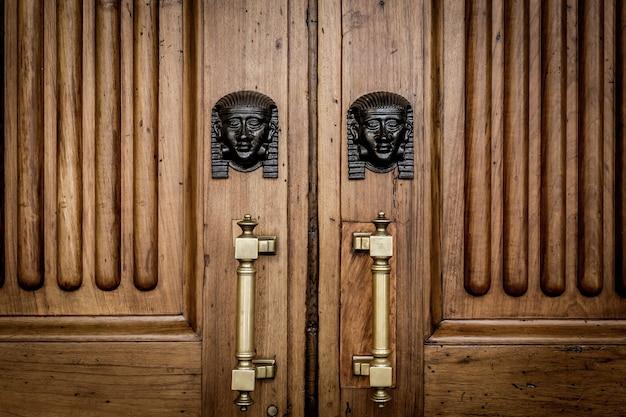 Dettaglio di due teste di sfinge in bronzo su una vecchia porta di legno - circa 100 anni, palazzo italiano nel nord italia