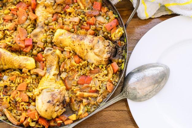 Dettaglio di una tipica padella per paella spagnola con riso con pollo e zafferano o paella di pollo, un cucchiaio da portata e un piatto bianco. cibo tipico spagnolo.