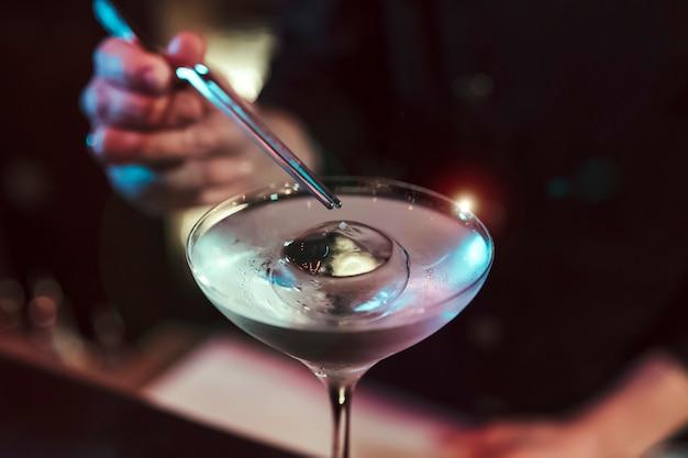 Dettaglio del barista sconosciuto mescolando cocktail. indossa un costume nero. è in un pub. uomo barbuto.